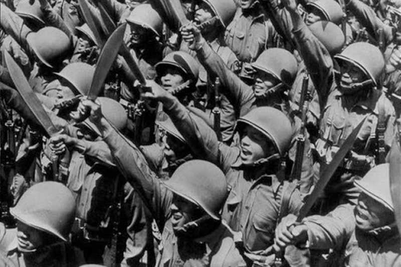 Several Filipino soldiers raise their knives into the air
