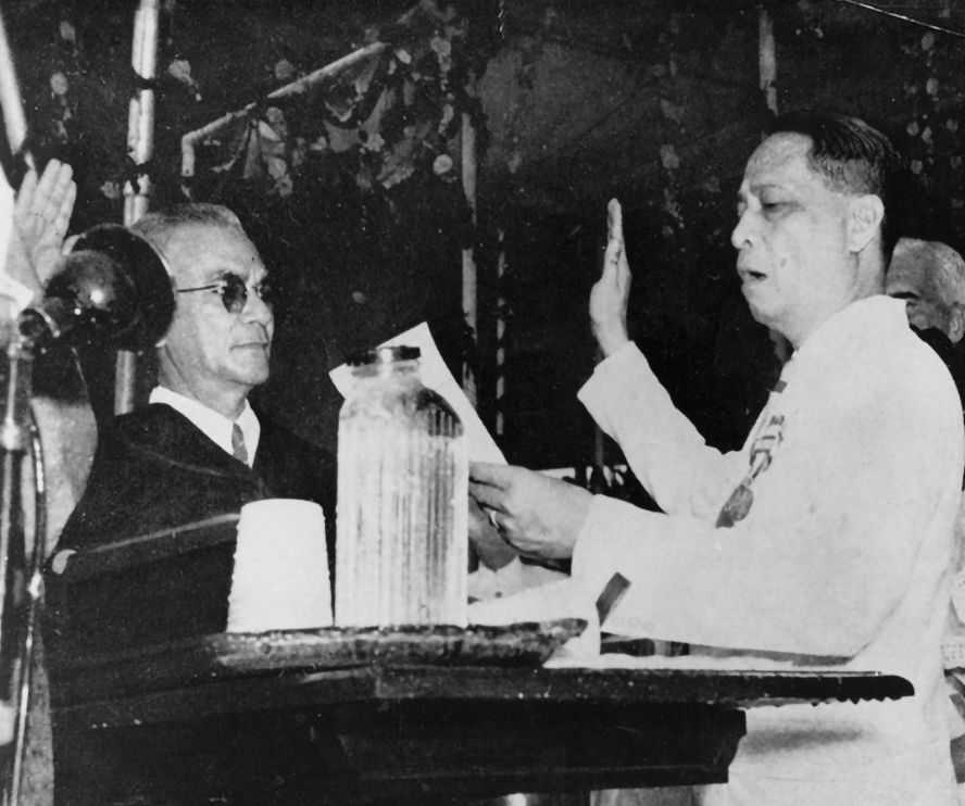 Black and white photo of President Manuel Roxas speaking over a podium and holding his right hand up in oath