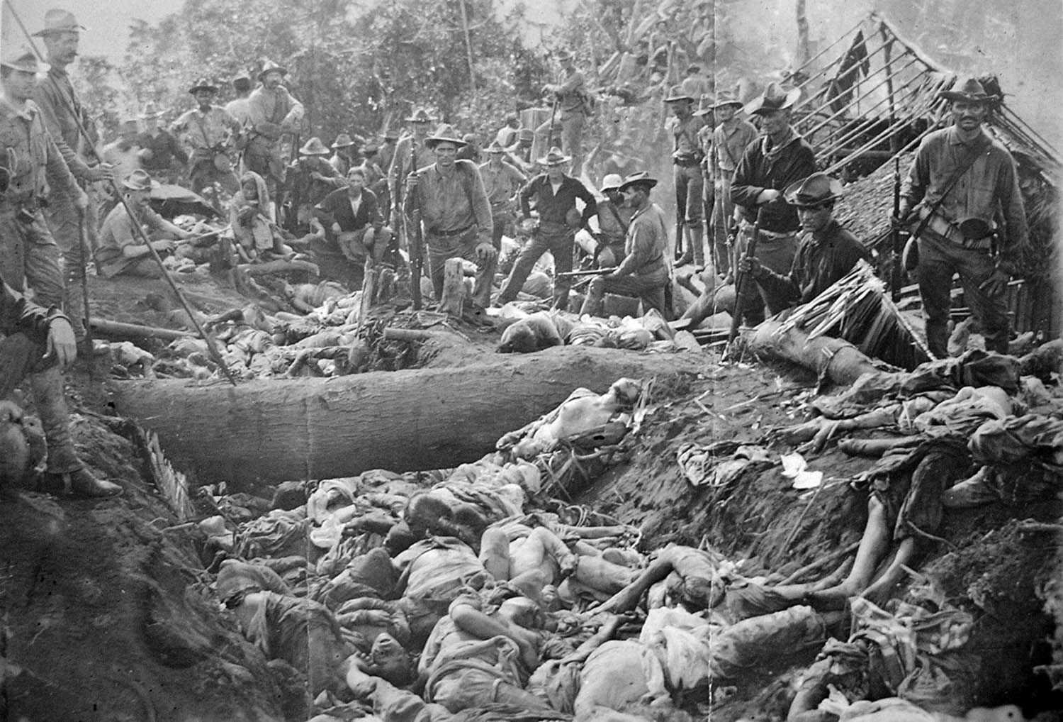 Black and white photo of American soldiers standing above hundreds of bodies of dead Filipinos