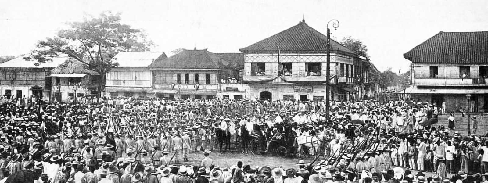 Black and white photo of many people gathered in a town center