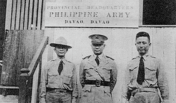 Black and white photo of three uniformed Filipino men standing under a sign that reads