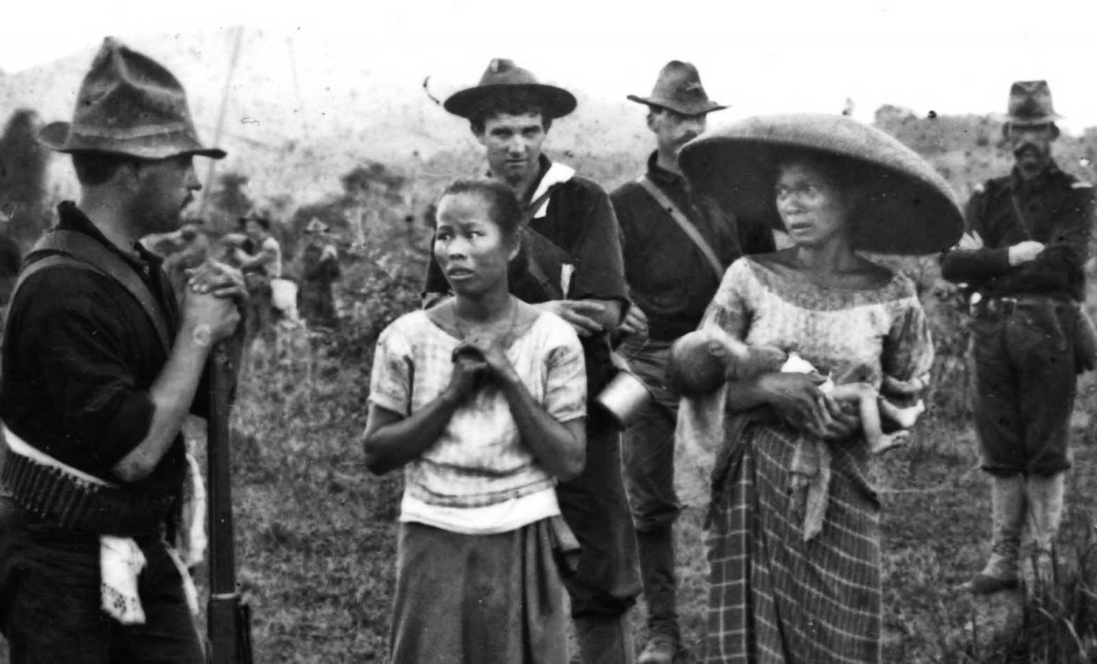 Black and white photo of Filipino women in a field (one holding a child) surrounded by American soldiers with rifles