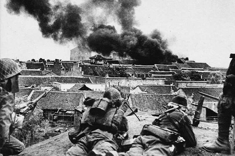 Black and white photo of Japanese soldiers laying on roof overlooking burning buildings