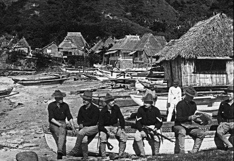 Black and white photo of American Soldiers seated on boat in a Filipino village