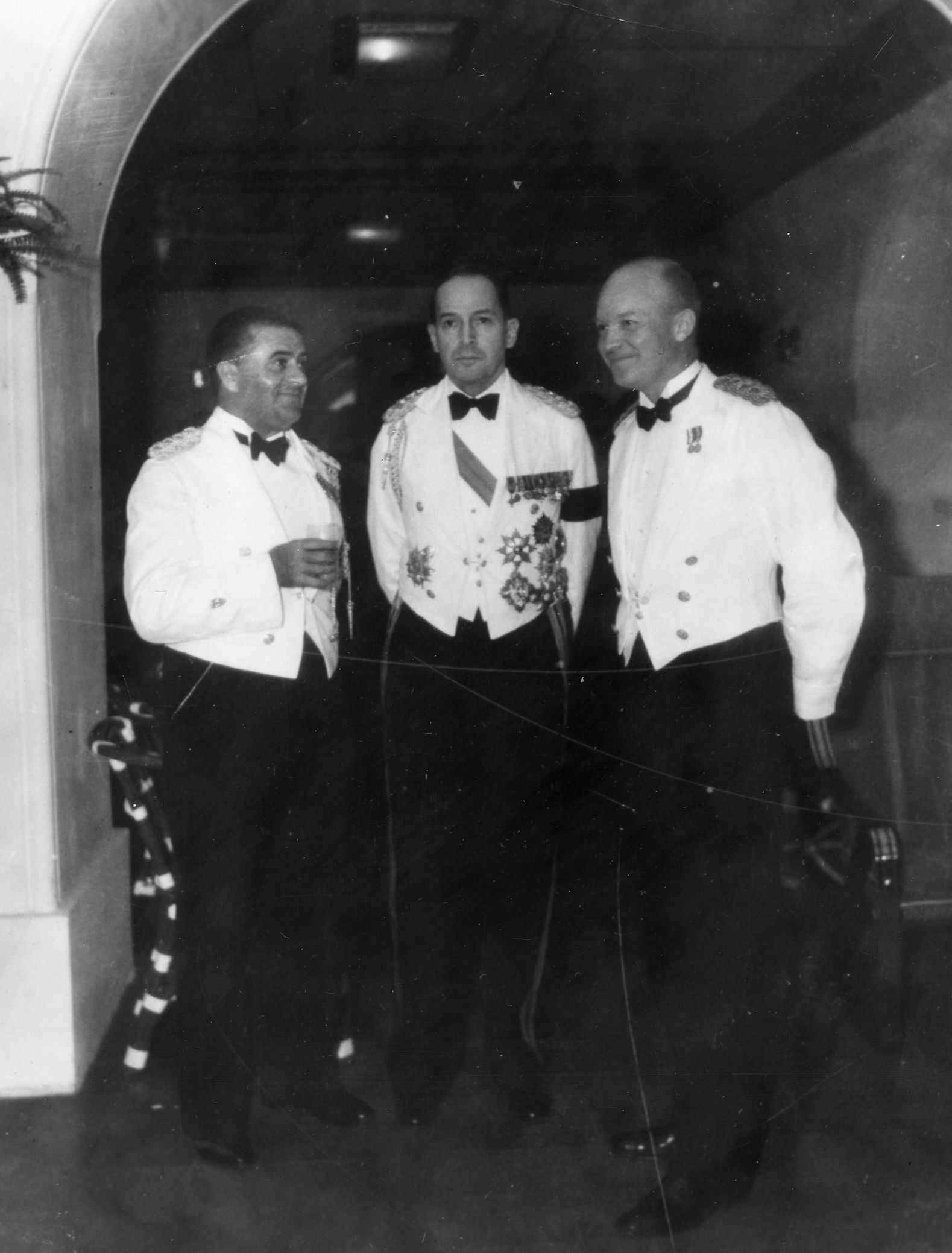 Black and white photo of Eisenhower, MacArthur, and Davis in formal dress.