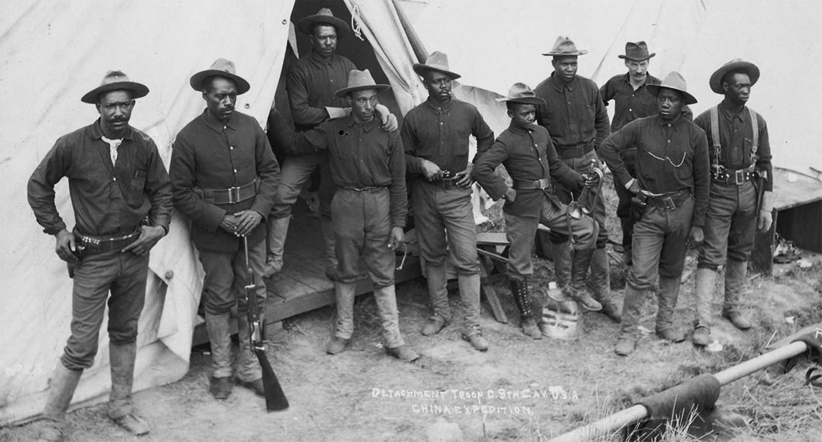 Black and white photo of African American soldiers standing outside their tent in uniform, some holding rifles