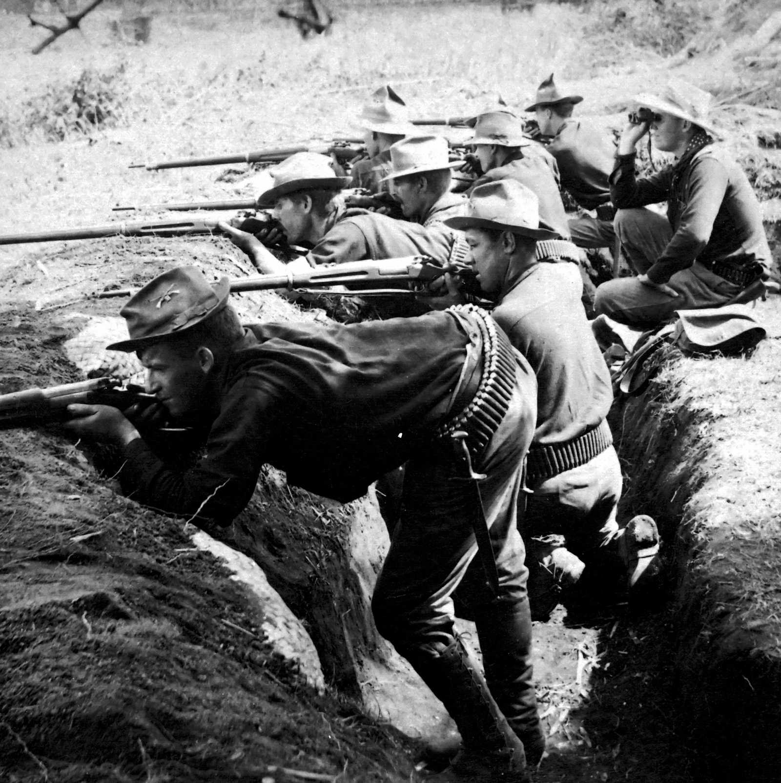 Black and white photo of soldiers aiming their rifles out of a trench