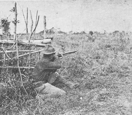 Black and white photo of crouching soldier aiming rifle into field