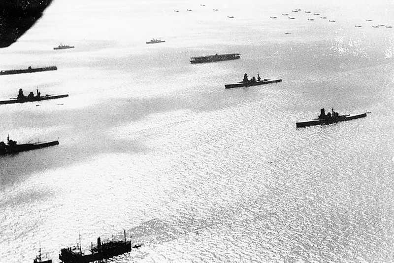Black and white aerial photo of battleships cruising through the ocean