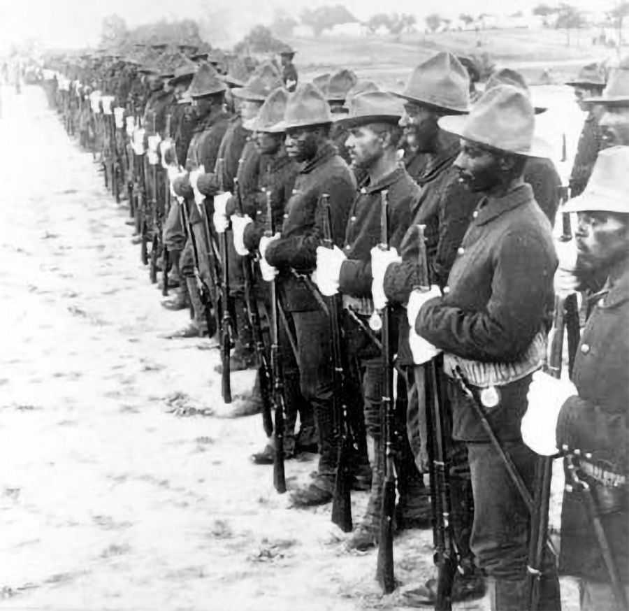 Black and white photo of African American soldiers lined up in uniform and holding their rifles