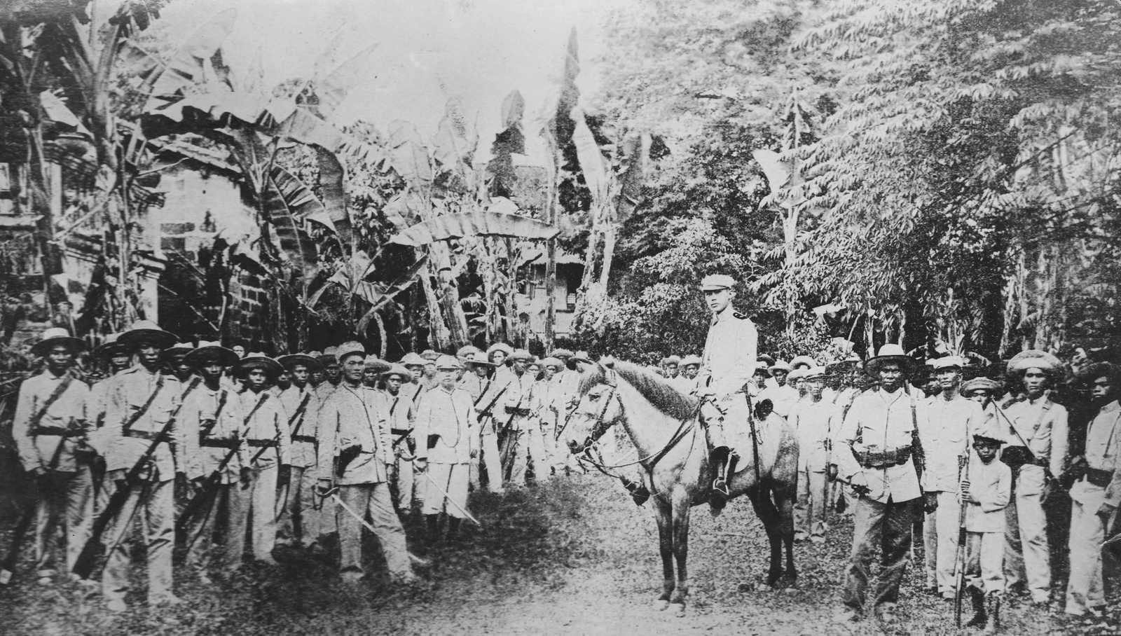 Black and white photo of Filipino soldiers in uniform and holding rifles in the jungle, with one man seated on a horse.