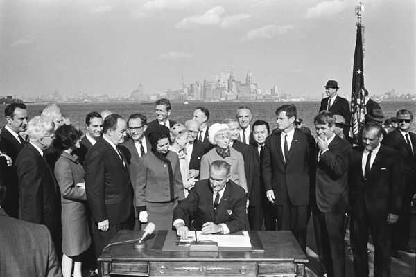 Lyndon Johnson signs the immigration act with New York City in the background